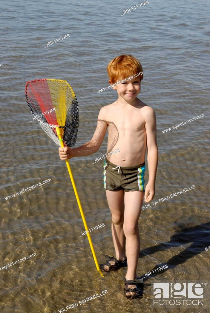 Stock Photo: Boy on the beach, seaside with fishing net at the Adria, Bibione, Venetia, Venice, Italy, Europe.