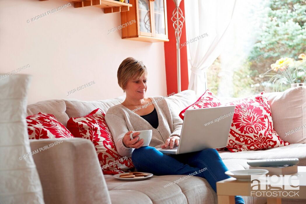 Stock Photo: Mother enjoying surfing on the net while relaxing at home with coffee.