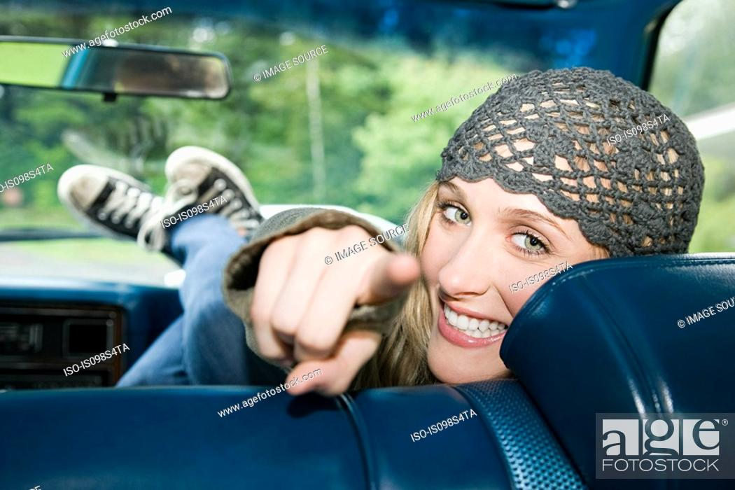Stock Photo: Young woman in car pointing at camera.