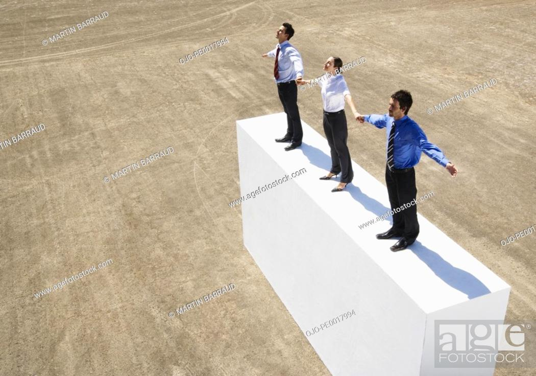 Stock Photo: Three businesspeople standing on wall outdoors holding hands.
