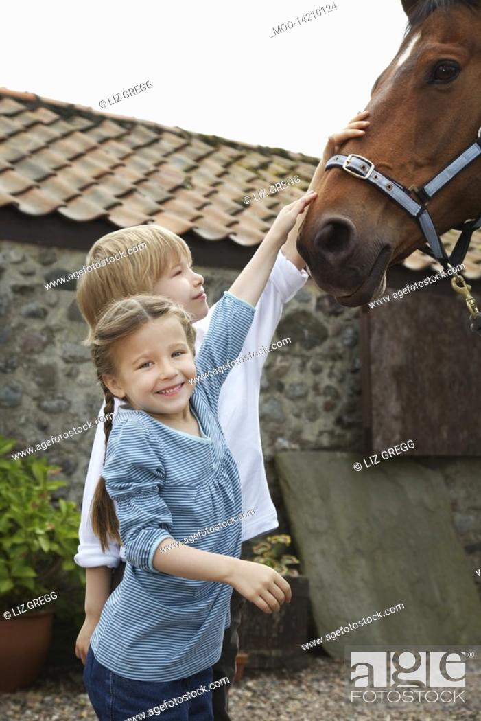 Stock Photo: Sister and brother 5-6 7-9 stroking horse outside stable.