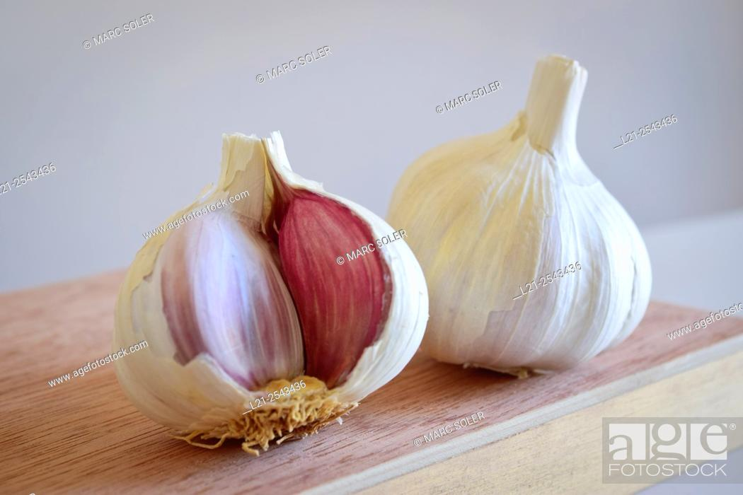 Stock Photo: Garlic. Two garlics on a wooden surface.