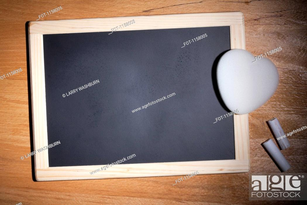 Stock Photo: A small blank chalkboard with chalk and a heart shaped eraser.