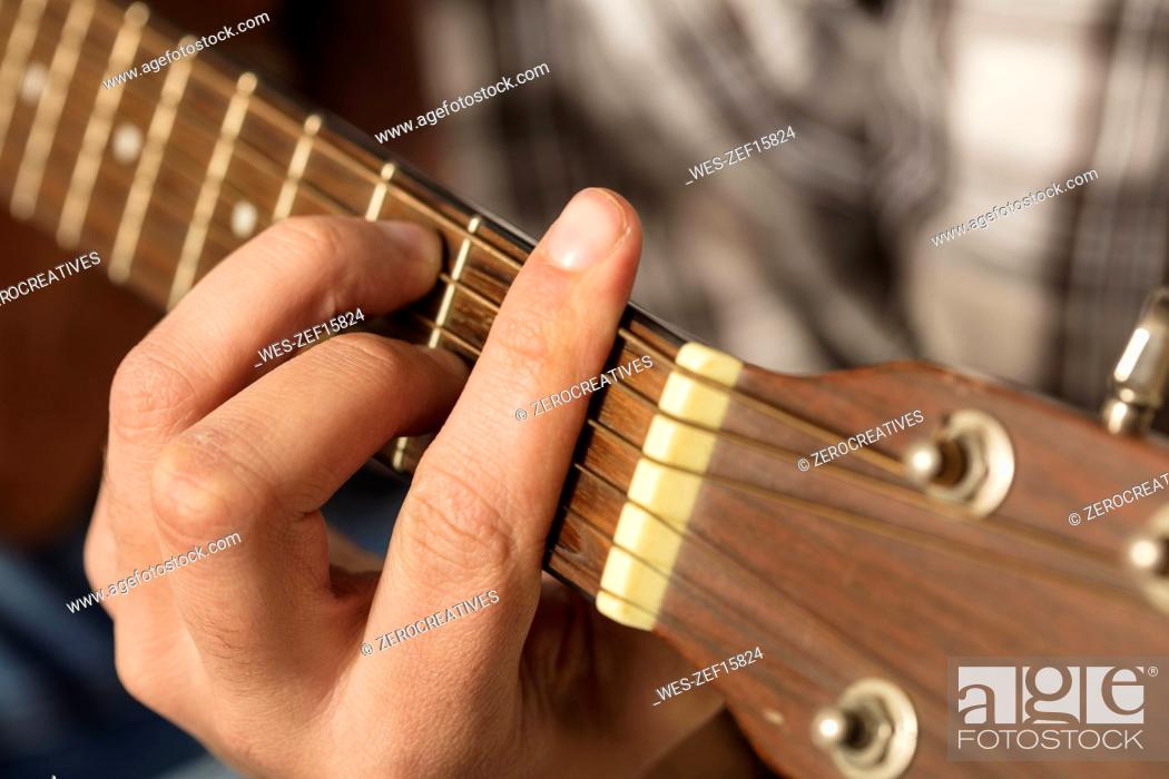 Imagen: Close-up of man's hand playing guitar.