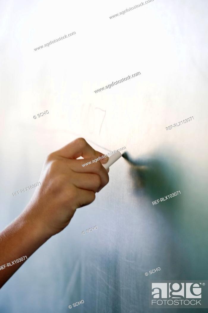 Stock Photo: Hand writing numbers on blackboard in classroom.