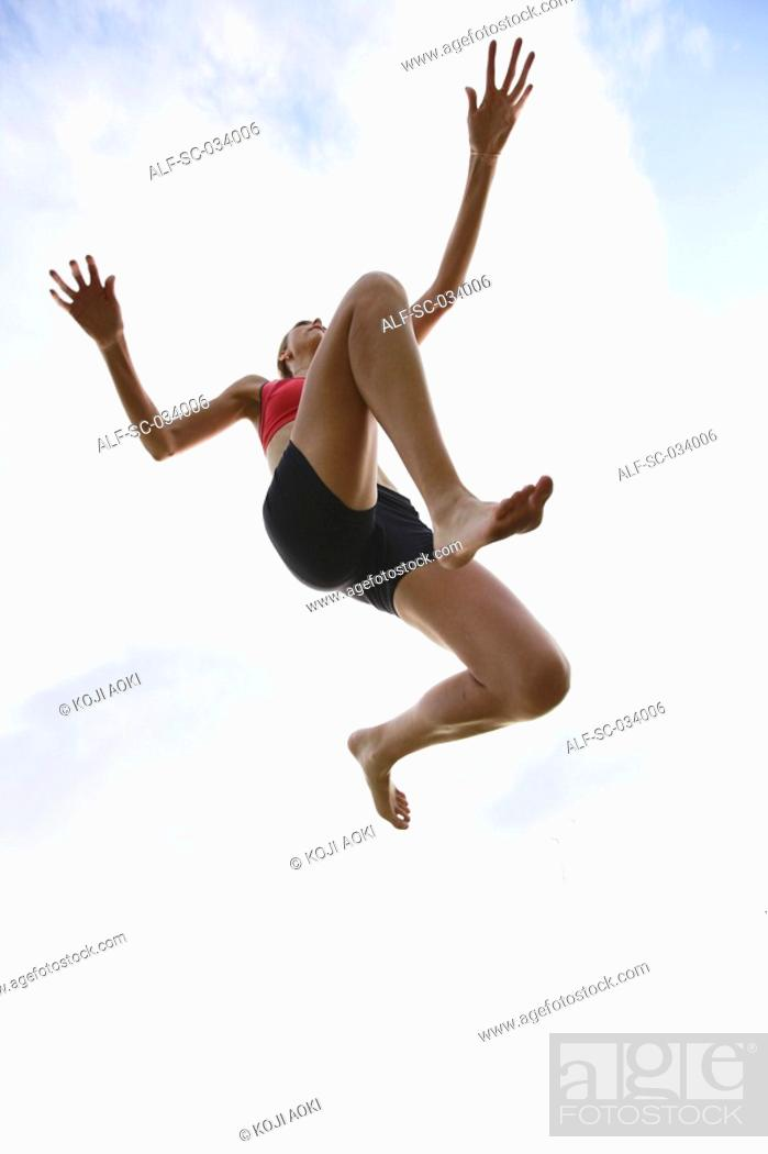 Stock Photo: Young Woman jumping in the air.