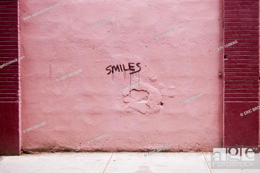 Stock Photo: The word 'smiles' is written on a pink wall.