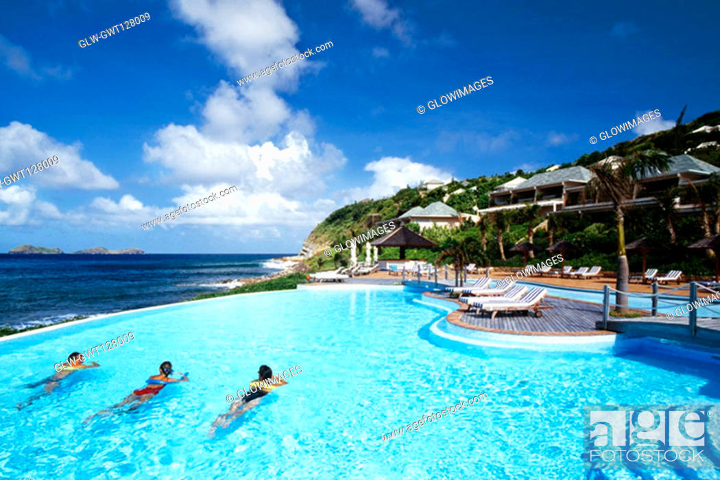 Stock Photo: Three people relaxing in a swimming pool of a resort near a seashore, St. Bant's.