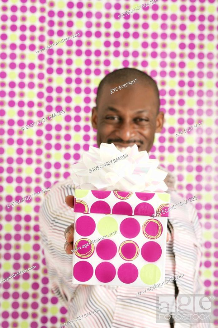 Stock Photo: African American man holding birthday gift.