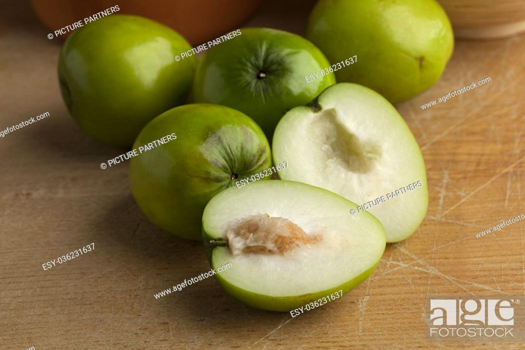 Photo de stock: Fresh green whole and half Ambarella fruit with a fibrous pit.