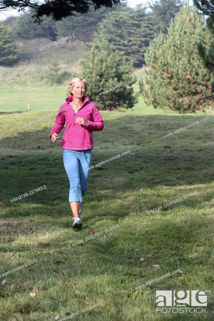 Stock Photo: Young blonde woman outdoors. Jogging in countryside.