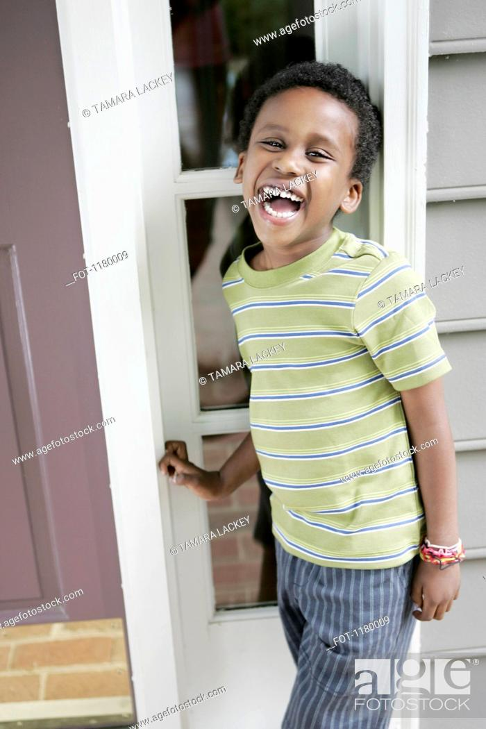 Stock Photo: A cheerful laughing boy standing at the front door of his house.