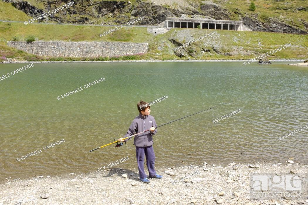 Stock Photo: Boy fishing in the lake Foscagno, Lombardy, Italy.