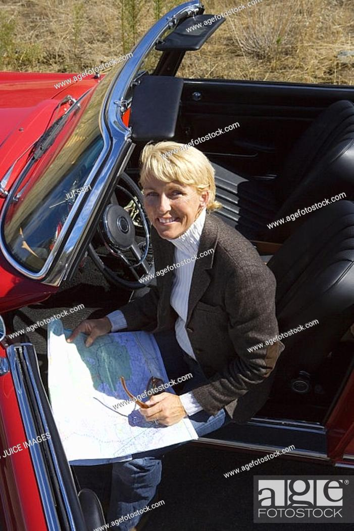 Stock Photo: Mature woman sitting in red convertible car, looking at road map, smiling, portrait, elevated view.