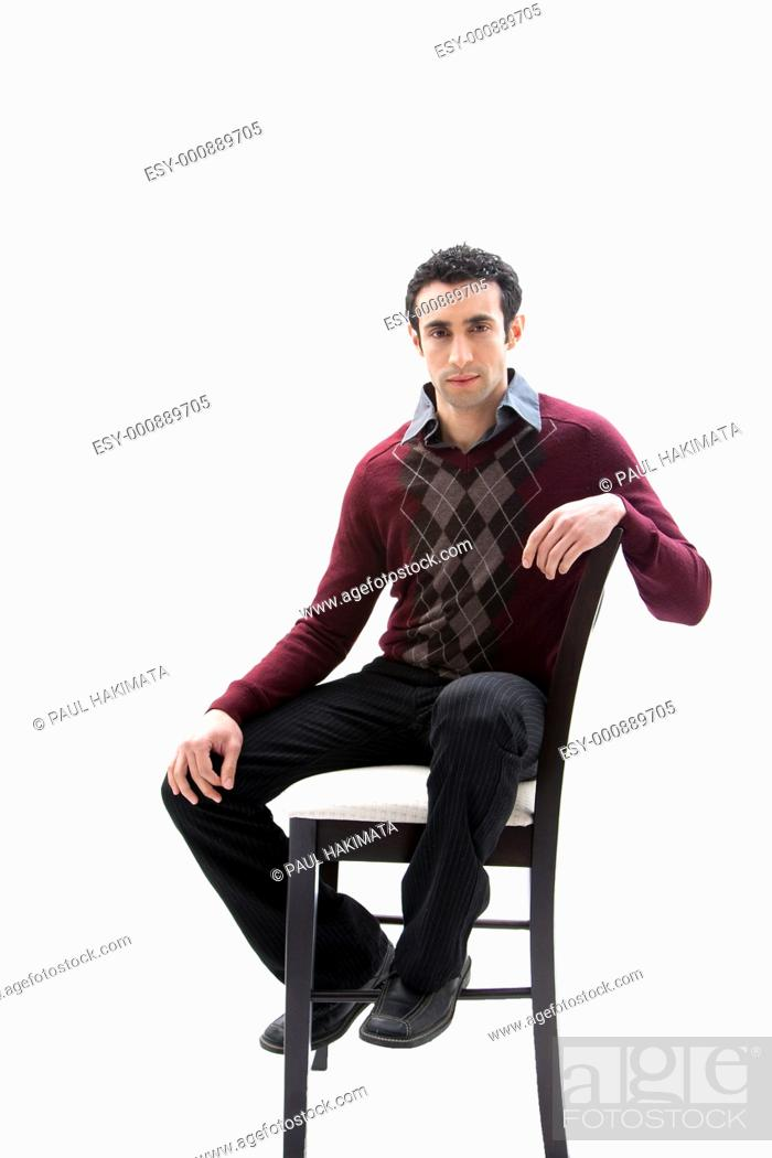 Stock Photo: Handsome guy wearing business casual clothes sitting on a high chair, isolated.
