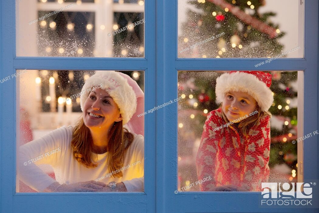 Stock Photo: Mother & daughter looking out of the window waiting for Santa to arrive.