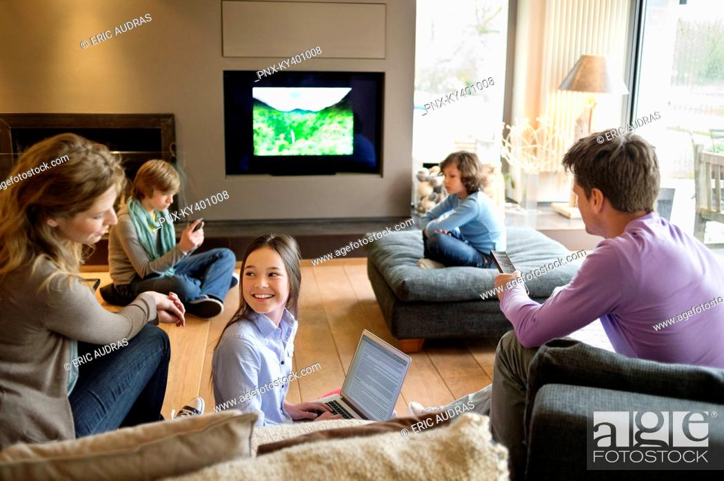Stock Photo: Family using electronic gadgets in a living room.