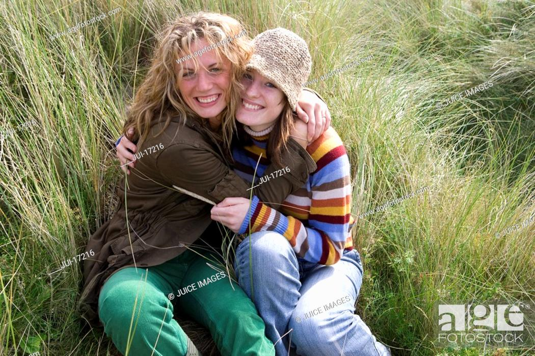Stock Photo: Young women hugging each other in grass.