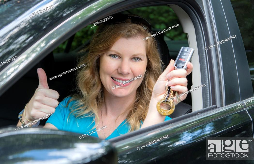 Stock Photo: Young teenage girl age 16 with first driving of a car showing off her keys MR model released.