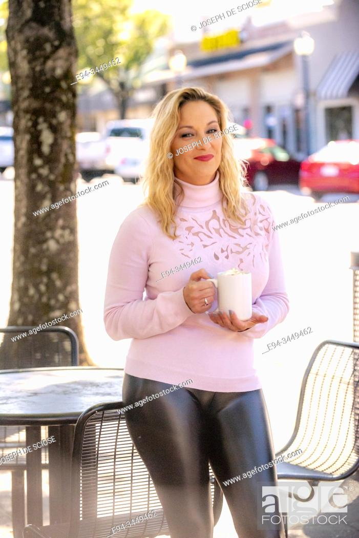 Photo de stock: A pretty 40 year old blond woman on a city street, holding a cup of coffee and looking at the camera.