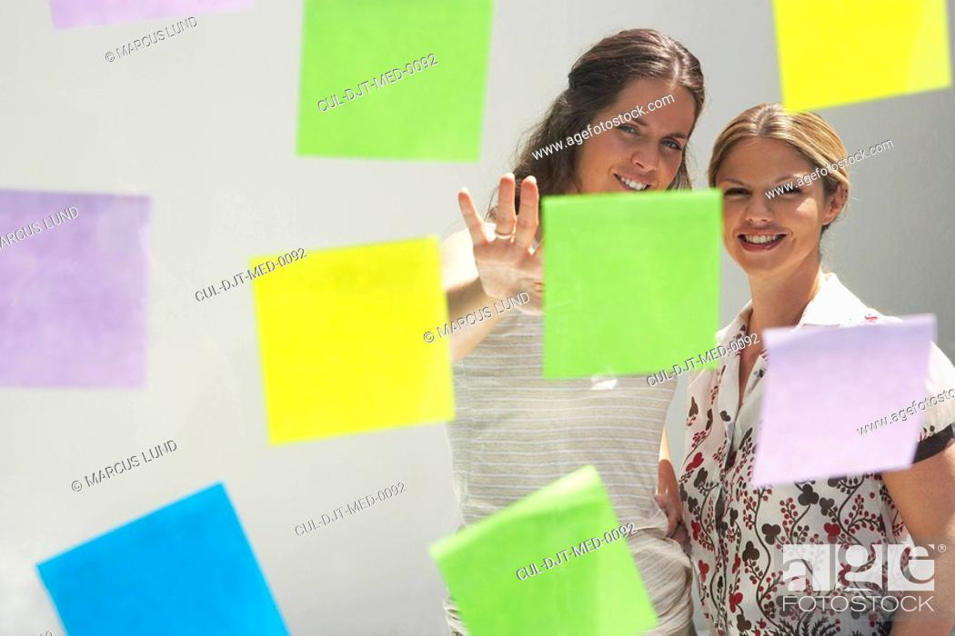 Stock Photo: Two young women seen through window with colored swatches / PostIt Notes.