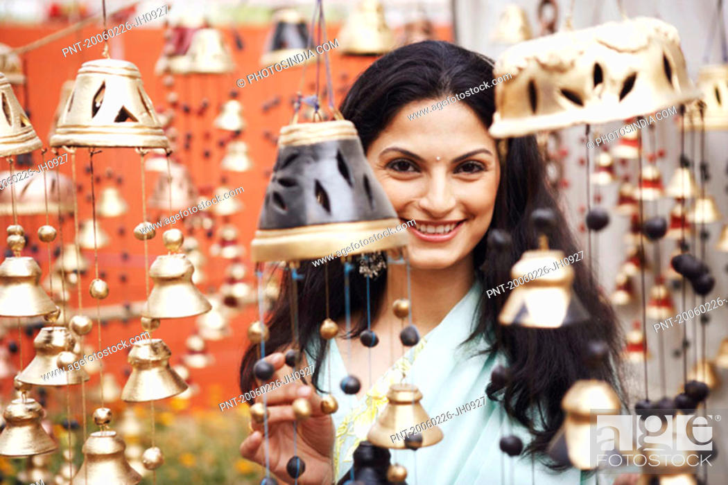 Stock Photo: Portrait of a young woman choosing bells.