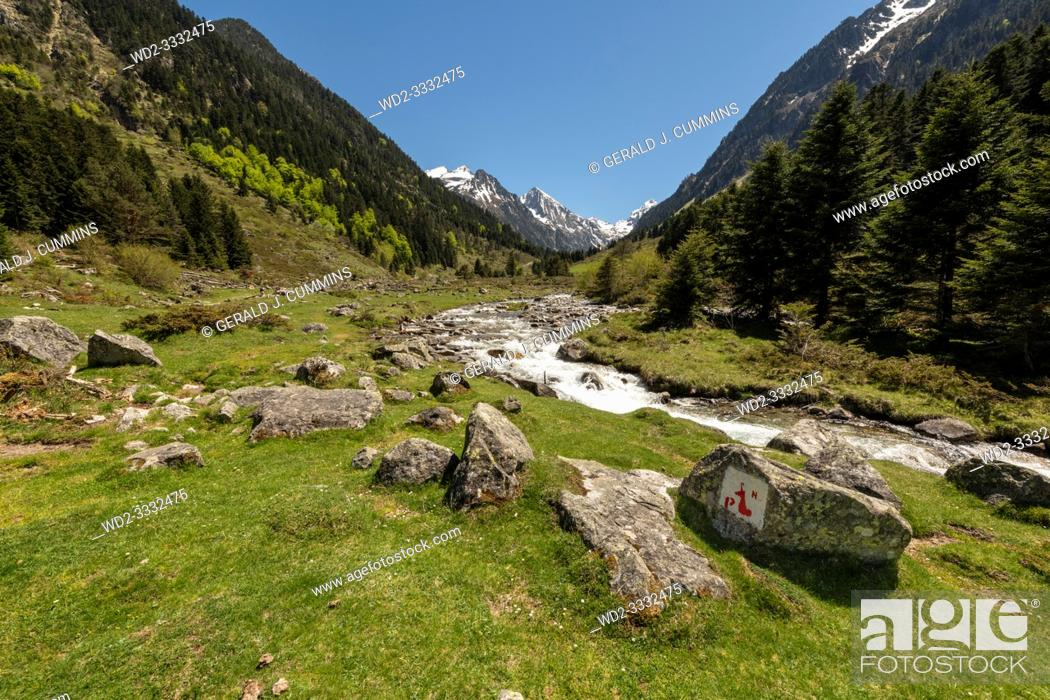 Stock Photo: Europe, France, Pyrenees, 05-2019, Water streams from melting snow cut through a valley in the mountains of French Pyrenees.