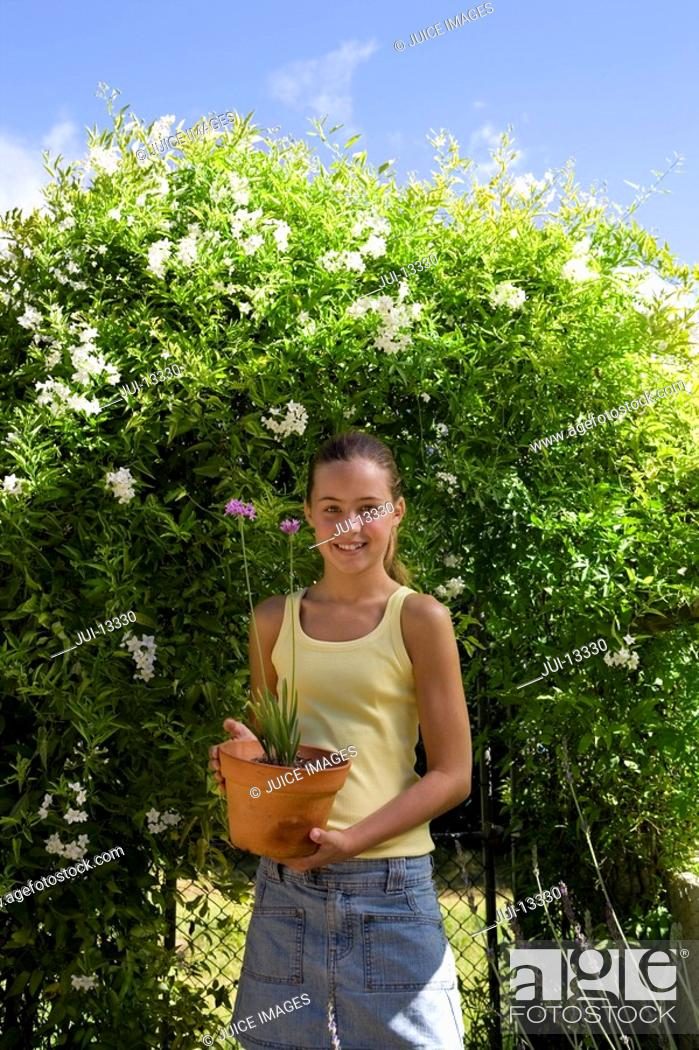 Stock Photo: Girl 10-12 with flower pot by hedge, smiling, portrait.