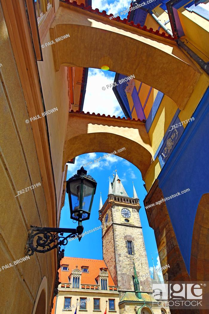 Stock Photo: Old Town Hall clock tower seen through an arch wtih a street lamp in Old Town Square in Prague, Czech Republic.