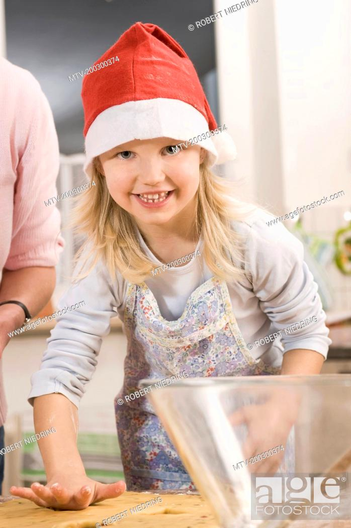 Stock Photo: Mother and daughter preparing cookies, smiling.