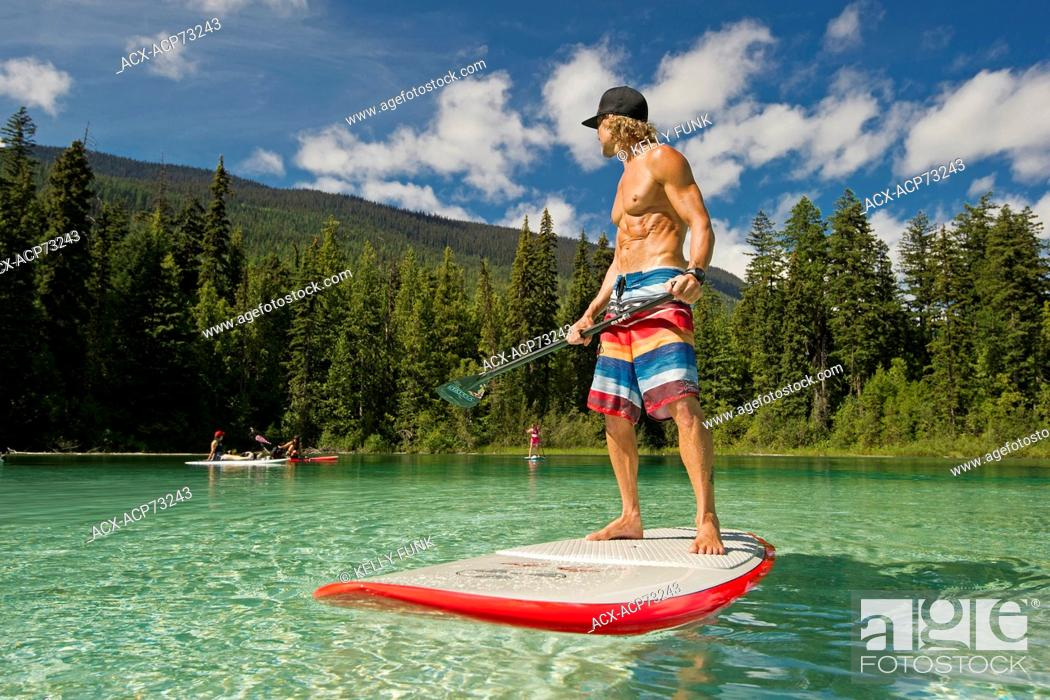 Stock Photo: A paddle boarder checks on his group while on the beautiful waters of Johnson Lake, North of Kamloops in the Thompson Okanagan region of British Columbia.