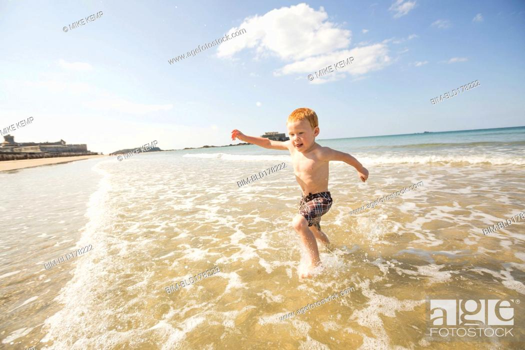 Stock Photo: Caucasian boy playing in waves on beach.