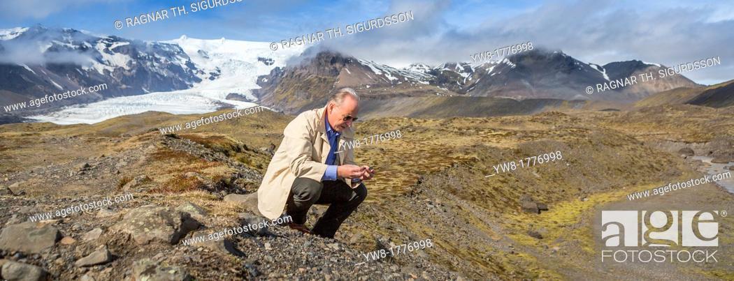 Stock Photo: Scientist investigating the landscape, Kviarjokull Glacier in background, Vatnajokull Ice Cap, Iceland.