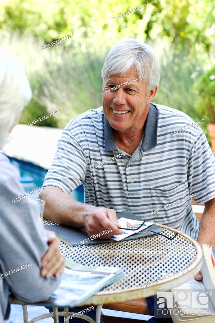 Stock Photo: Couple sitting at patio table outdoors.