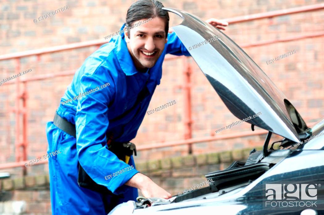 Stock Photo: Smiling young mechanic repairing car.