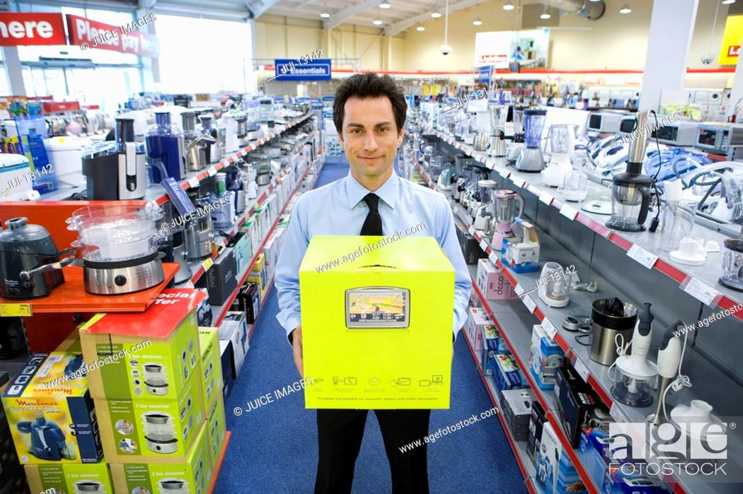 Stock Photo: Young man with box in electronics aisle, smiling, porttrait.