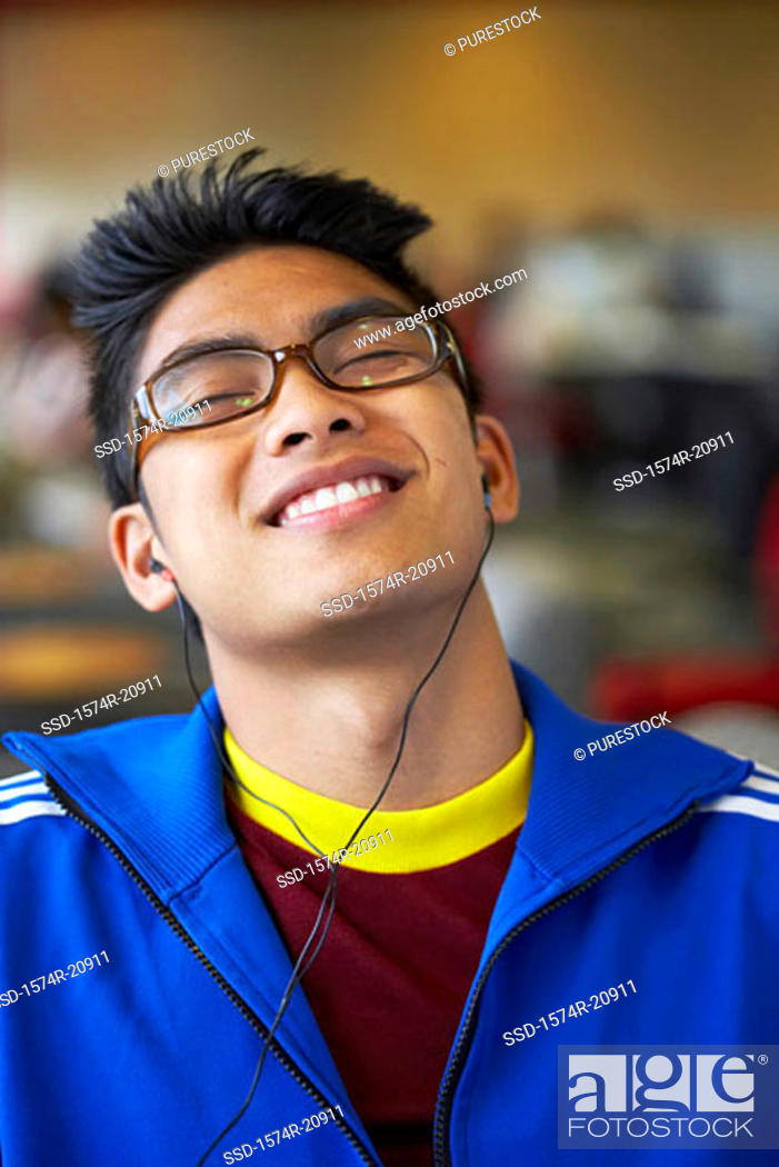 Stock Photo: Close-up of a college student wearing headphones and listening to music.