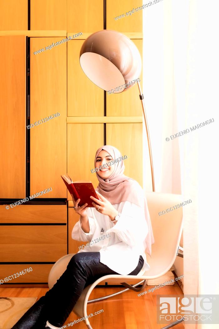Stock Photo: Young muslim woman reading book.