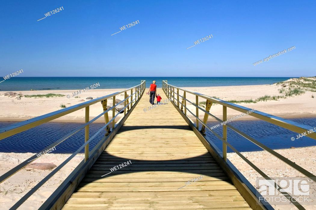 Stock Photo: Mother walking with kid. Bridge over Vääna river, Estonia. River mouth at Baltic sea.