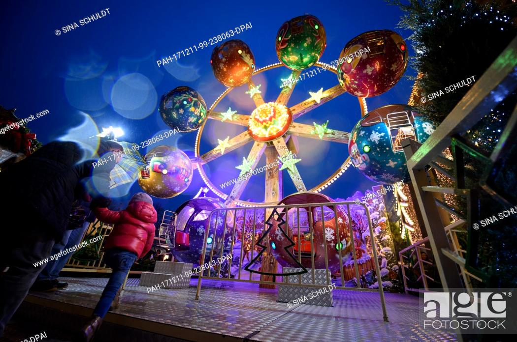 Stock Photo: A girl riding a carousel at the Christmas Market in Stuttgart, Germany, 11 December 2017. Photo: Sina Schuldt/dpa. - Stuttgart/Baden-Württemberg/Germany.