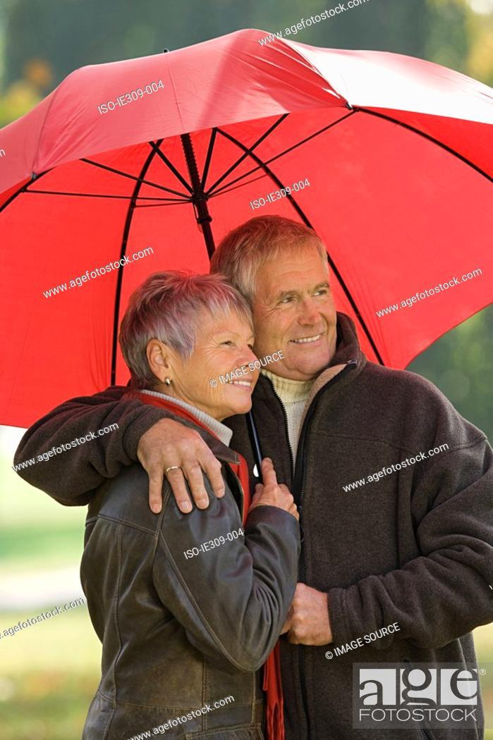 Stock Photo: Senior couple using a red umbrella.