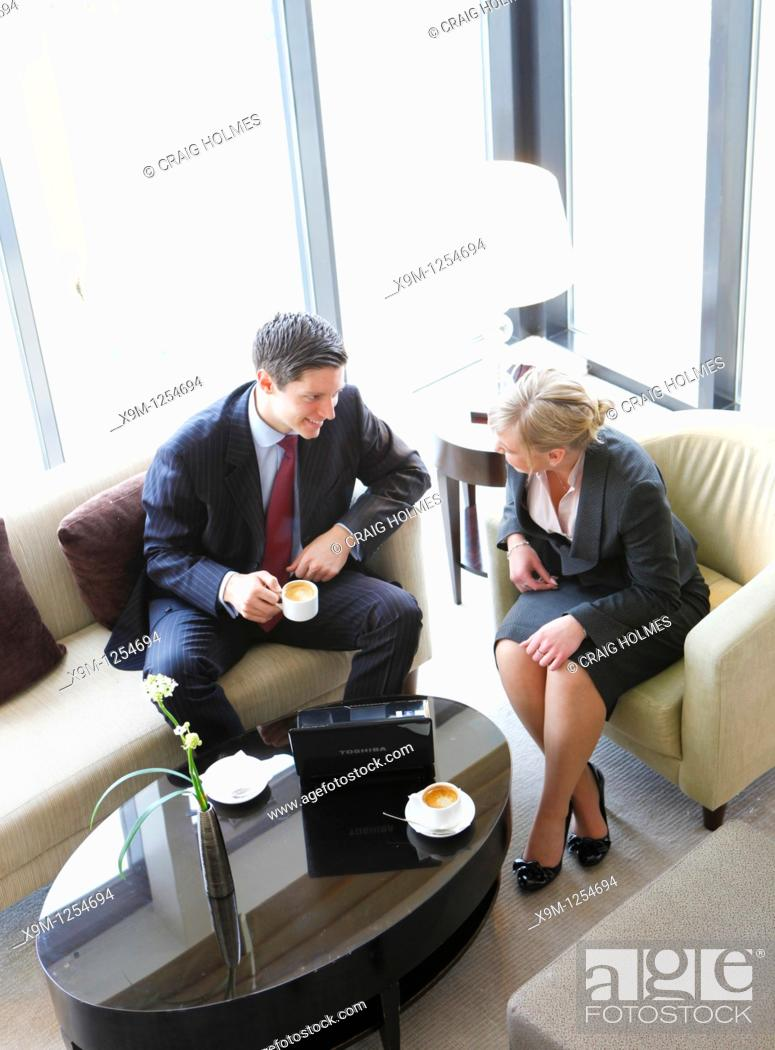 Stock Photo: Man and woman having a business meeting and coffee.