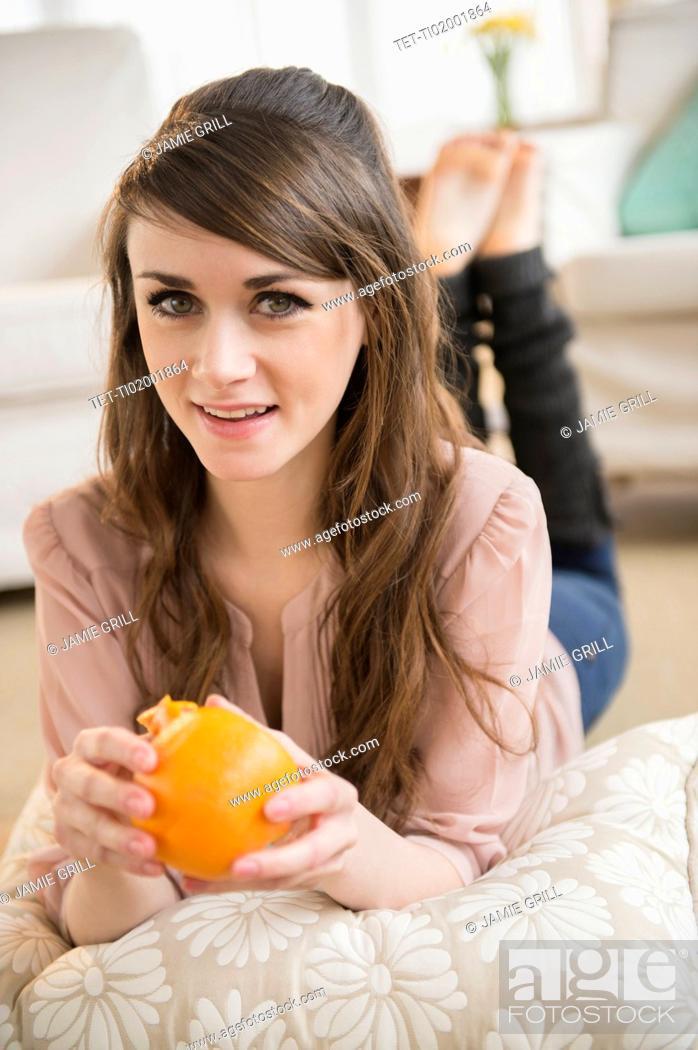 Stock Photo: Young woman eating orange.