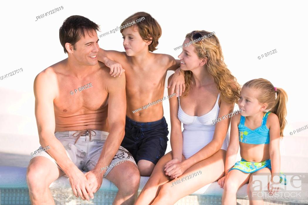 Stock Photo: Family sitting at the poolside and smiling.