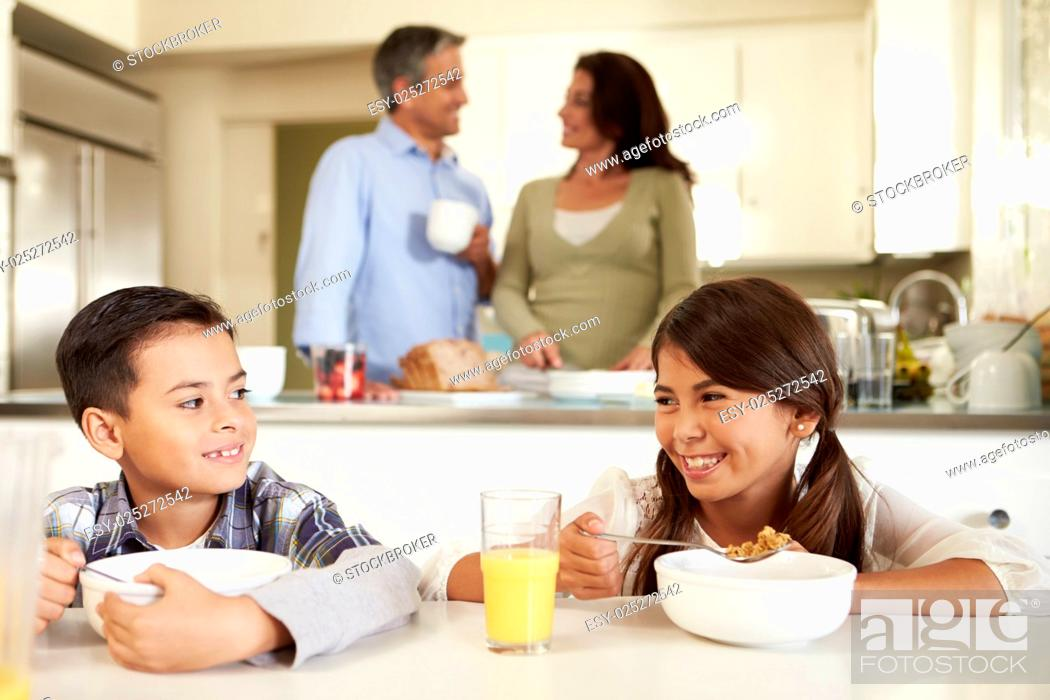 Photo de stock: Hispanic Family Eating Breakfast At Home Together.