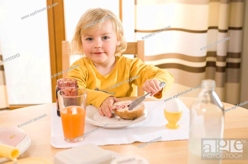 Stock Photo: Girl spreading jam on bread, smiling.