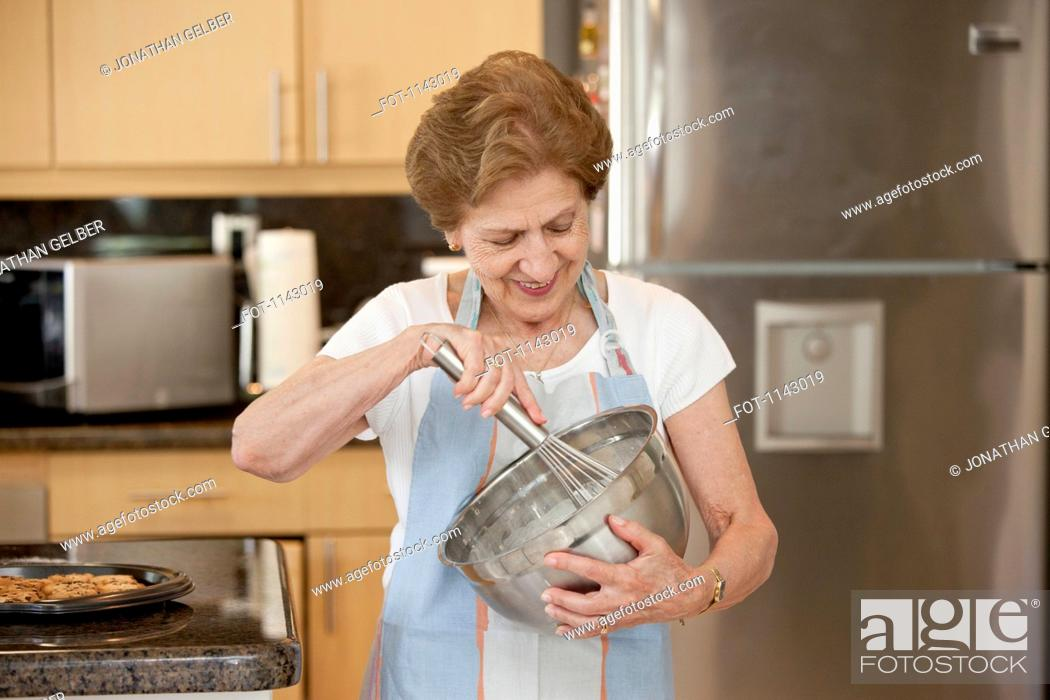 Stock Photo: A senior woman mixing ingredients in a bowl.