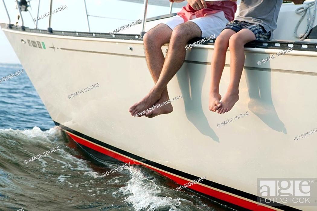 Stock Photo: Father and son sitting on yacht, legs dangling.