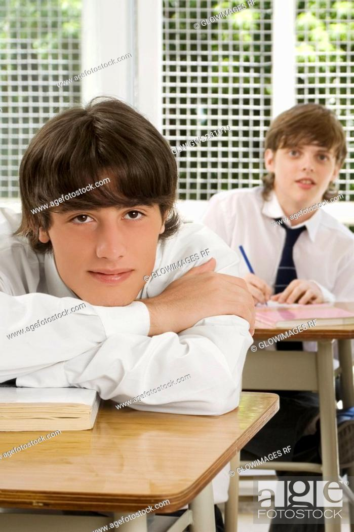 Stock Photo: Portrait of a young man leaning on a desk with a teenage boy sitting behind him in a classroom.