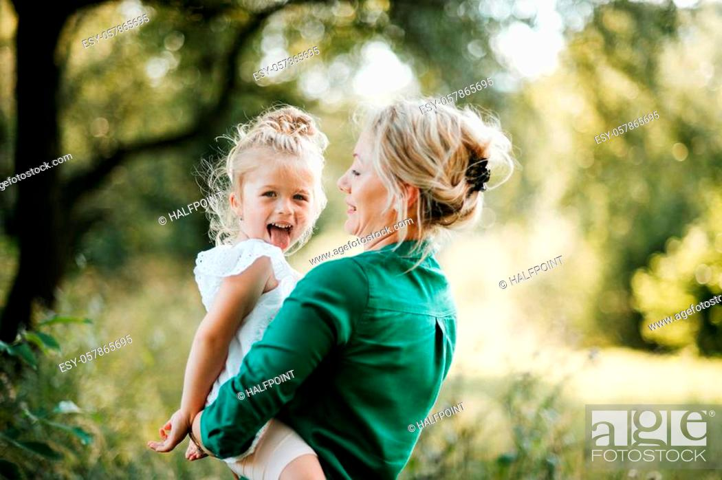 Stock Photo: Beautiful young mother in green sunny summer nature holding her cute small daughter in the arms, having fun. Copy space.